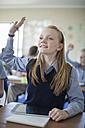 Schoolgirl in classroom raising her hand - ZEF004964
