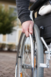 Hand of young man on spoke of wheelchair - WWF003665