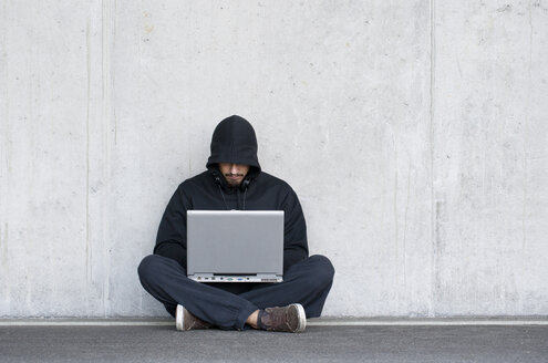 Hacker with laptop sitting in front of concrete wall - WWF003669