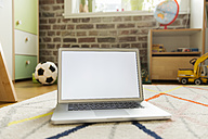 Laptop standing on carpet in children's room - MFF001404