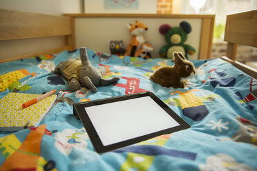 Tablet computer and soft toys on bed in children's room - MFF001411
