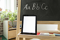 Tablet computer leaning at blackboard in children's room - MFF001414