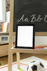 Tablet computer leaning at blackboard in children's room - MFF001420