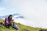 Austria, Altenmarkt-Zauchensee, young woman sitting on alpine meadow - HHF005078