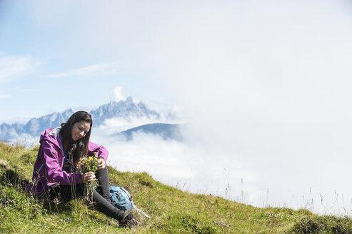 Austria, Altenmarkt-Zauchensee, young woman sitting on alpine meadow - HHF005078