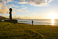 Easter Island, Hanga Roa, Traveller and Moai stone figurine in the Tahai Ceremonial Complex at sunset, archaeological site - GEMF000019