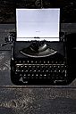 Old black typewriter on dark wood - MAEF009494