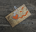 Metal heart with orange pebbles on wooden chopping board - MGOF000047