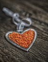 Metal heart with orange pebbles on wooden background, Studio shot - MGOF000048