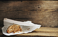 Home-made pastry on paper bag in front of wooden background - BZF000029