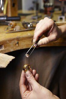 Goldsmith in workshop with gemstone and golden ring - EDF000096