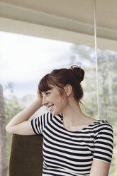 Smiling woman in front of windowpane - MFF001427
