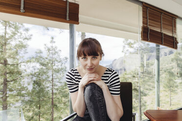Woman posing in chair in front of windowpane - MFF001435