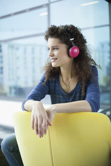 Smiling young woman wearing headphones at the window - RBF002315