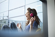 Screaming young woman wearing headphones at the window - RBF002324