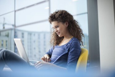 Smiling young woman using laptop at the  window - RBF002327
