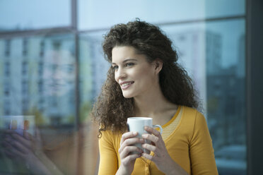 Smiling young woman with cup of coffee at the window - RBF002333