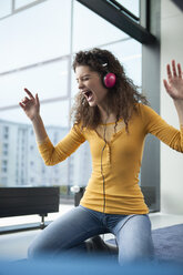 Screaming young woman wearing headphones at the window - RBF002310