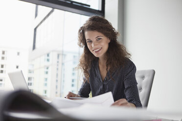 Portrait of young woman working at desk in office - RBF002349