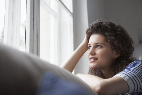 Young woman at home looking out of window - RBF002364