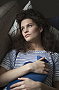 Serious young woman lying on sofa with hot water bottle - RBF002289