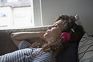 Young woman lying on couch wearing headphones - RBF002263