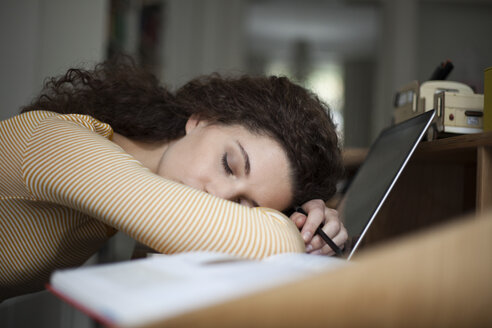 Overworked young woman sleeping on laptop in home office - RBF002273