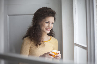 Smiling young woman peeling orange at the window - RBF002277