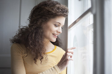 Smiling young woman painting heart on windowpane - RBF002278