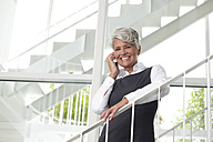 Smiling mature businesswoman on cell phone - MFRF000053