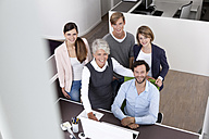 Happy business team at desk in office - MFRF000020