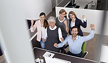 Happy business team celebrating at desk in office - MFRF000023