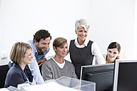 Smiling business team working on computer in office - MFRF000024