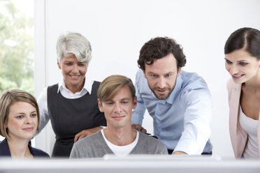 Smiling business team working on computer in office - MFRF000026