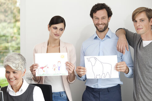 Businesswoman holding child's drawing and businessman holding paper with bull figure - MFRF000029