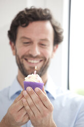 Smiling businessman holding birthday cupcake - MFRF000035