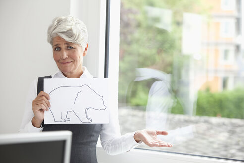 Mature businesswoman holding paper with bear figure - MFRF000011