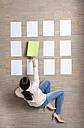Businesswoman sitting on floor organizing blank sheets of paper - MFRF000044