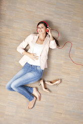Young woman lying on floor listening to music - MFRF000047