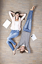 Smiling man and woman lying on floor with laptop and digital tablet - MFRF000049