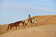 USA, Wyoming, cowgirl with two horses in badlands - RUEF001436