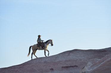 USA, Wyoming, cowgirl riding in badlands - RUEF001444