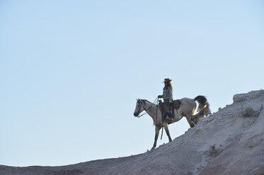 USA, Wyoming, cowgirl riding in badlands - RUEF001445