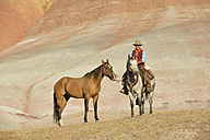 USA, Wyoming, cowboy with two horses in badlands - RUEF001458