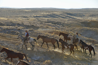 USA, Wyoming, cowboy and cowgirl leading horses in badlands - RUEF001470