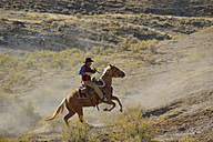 USA, Wyoming, cowboy riding in badlands - RUEF001474