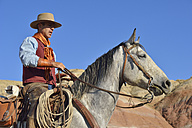 USA, Wyoming, cowboy on his horse in badlands - RUEF001484