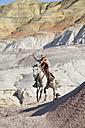 USA, Wyoming, Big Horn Mountains, riding cowboy swinging lasso - RUEF001504