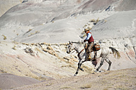 USA, Wyoming, cowboy riding in badlands - RUEF001509