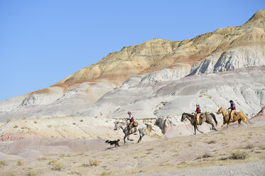 USA, Wyoming, two cowboys and cowgirl riding in badlands - RUEF001510